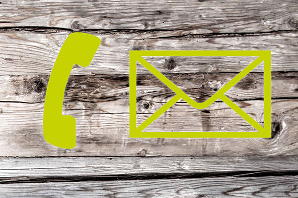 On a wooden background you can see green symbols of a telephone and an envelope.