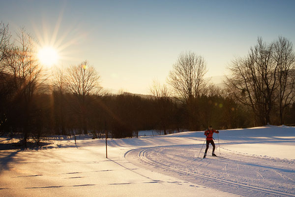 Cross-country skier runs at sunset.