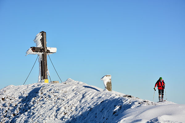 A climber is on a snow-covered mountain. The summit cross is on his left.