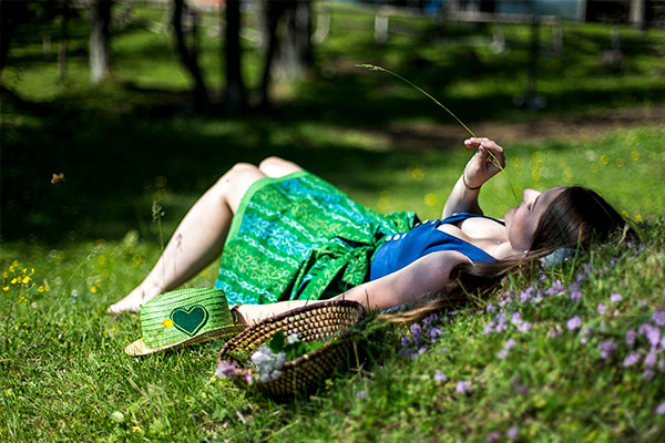 A woman in a dirndl lies in the meadow under a tree.